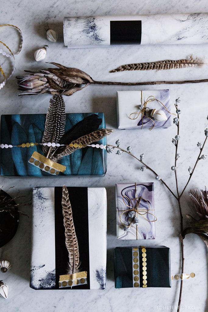 moderne und edle Geschenkverpackung für Weihnachten mit gold und Federn
