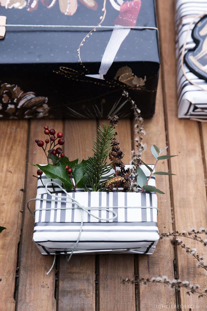 natuerliche Weihnachtsgeschenkverpackung mit Tannen und Beeren