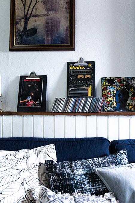 wohnzimmer-im-urban-stil-mit-vielen-kissen-cds-und-antikem-wandbild
